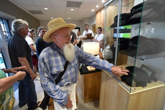 "William Staats, of Vero Beach, picks up a free hat after making his purchase of marijuana medication at the new Trulieve, a medical marijuana dispensary, on their opening day in April 2018 on Commerce Avenue in Vero Beach. ""Great, very convenient."""