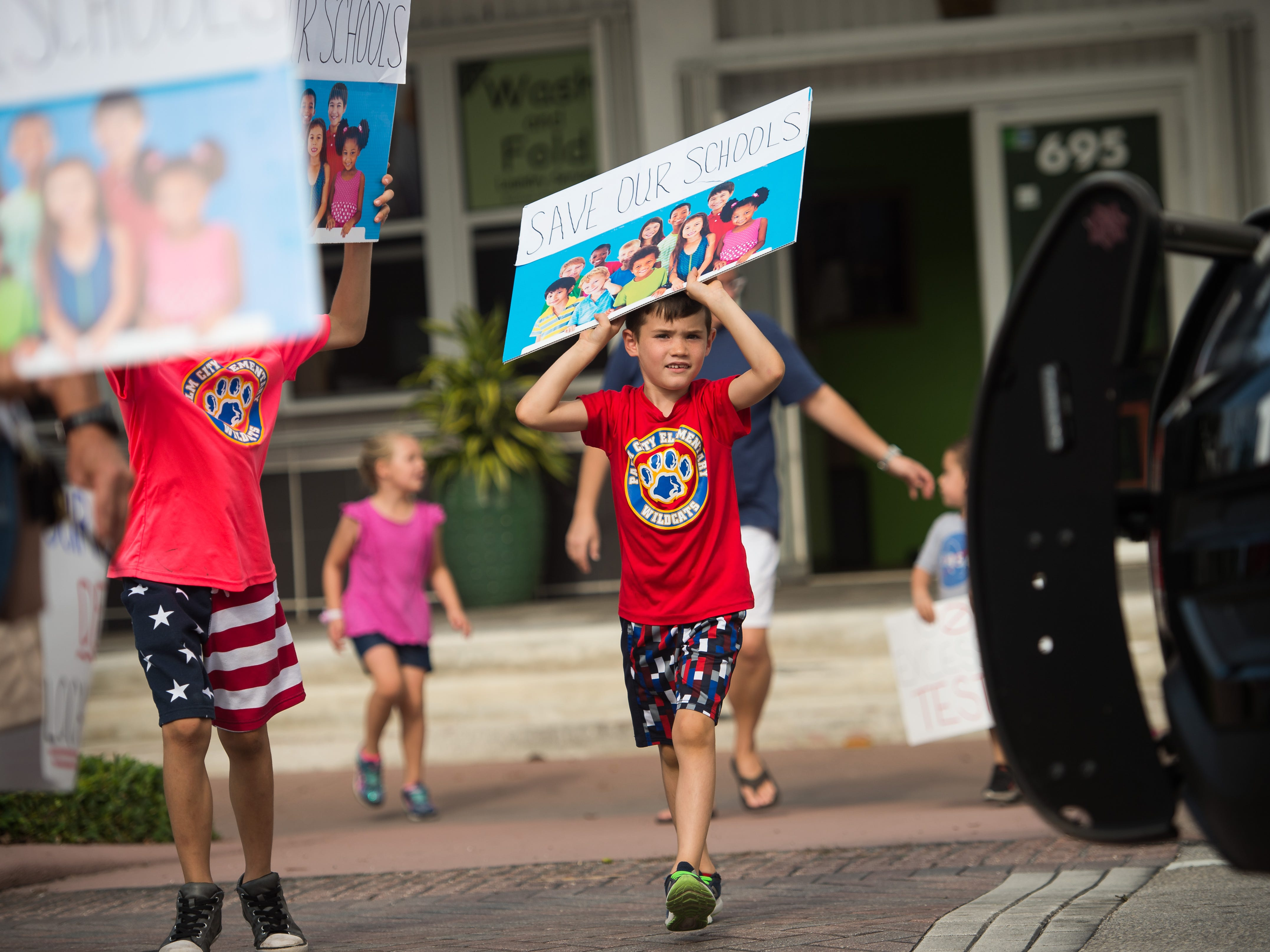 "Beckett Davis, 6, of Palm City, crosses Colorado Avenue while Stuart police direct traffic during a march in support of reforms to Florida's public education system Wednesday, May 15, 2019, in Stuart. His mother, Corinne Davis, said the family moved to Martin County for the quality of schools. ""I just want to make sure their future is set up in a way that's, you know, really positive, and that it's a good experience,"" she said. The event was organized by the Facebook group page ""Reconstruct-ED: A Message to Governor DeSantis,"" which lists over-testing and low teacher pay among its concerns."