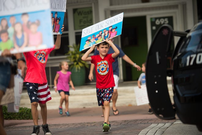 """Beckett Davis, 6, of Palm City, crosses Colorado Avenue while Stuart police direct traffic during a march in support of reforms to Florida's public education system Wednesday, May 15, 2019, in Stuart. His mother, Corinne Davis, said the family moved to Martin County for the quality of schools. """"I just want to make sure their future is set up in a way that's, you know, really positive, and that it's a good experience,"""" she said. The event was organized by the Facebook group page """"Reconstruct-ED: A Message to Governor DeSantis,"""" which lists over-testing and low teacher pay among its concerns."""