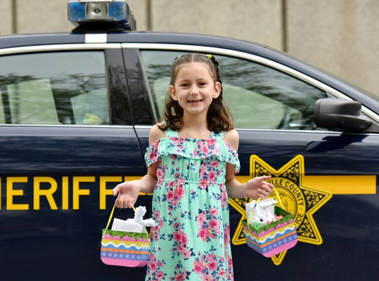 Anabel Hawthorne, 8, holds gift baskets that she dropped off at the Greenville County Sheriff's Office in Greenville as part of the Adopt-a-Cop program.