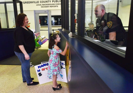 Anabel Hawthorne, 8, middle, and her mother Jennifer Hawthorne talk with deputy J. Shetley and the Greenville County Sheriff's Office in Greenville while dropping off gifts as part of the Adopt-a-Cop program on Saturday, April 13, 2019.