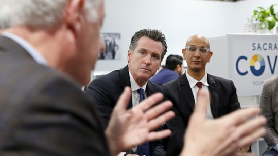 California Gov. Gavin Newsom, second from left, listens as John Arensmeyer, founder and chief executive officer of Small Business Majority, left, discusses the problems small businesses have getting health insurance during a discussion with small business owners on Tuesday in Sacramento.