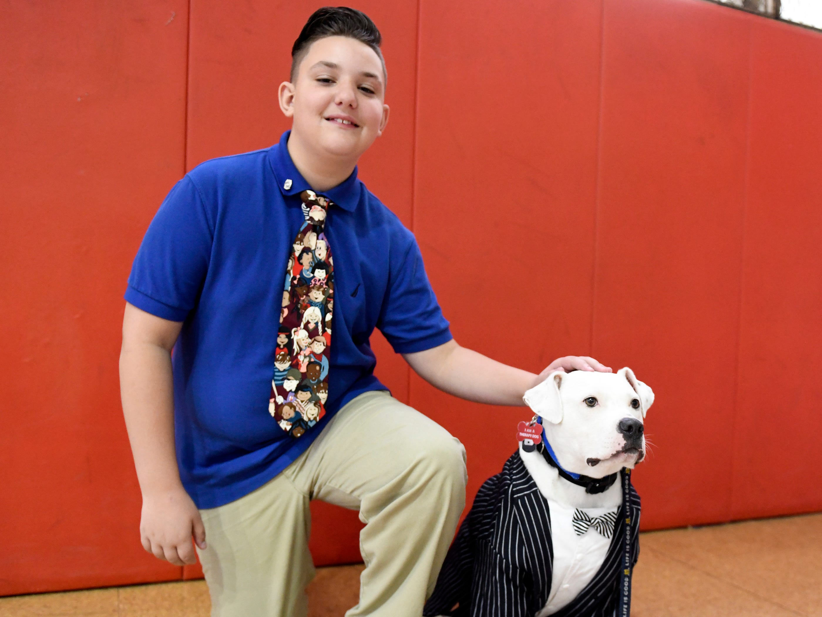 Nicholas Guaciaro pets Mennies Elementary School therapy dog Colefollowing the Giraffe Hero Award ceremony at the Vineland Public School District Administrative Offices on Wednesday, May 15, 2019.