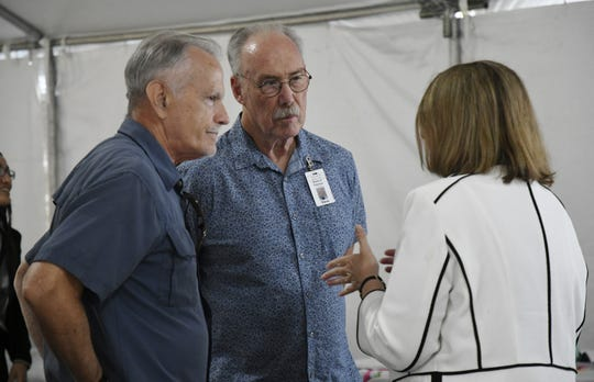 Tulare hospital district President Kevin Northcraft and Director Steven Harrell speak with Andrea Kofl of Adventist Health at a ceremony on Wednesday, May 15, 2019.