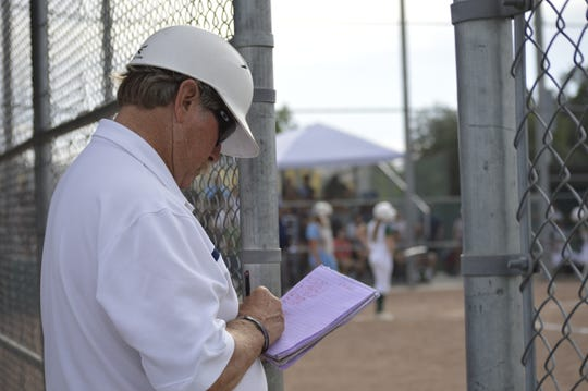 Redwood High School softball head coach Bob Rooney takes notes during a game against Kingsburg on May 14, 2019.