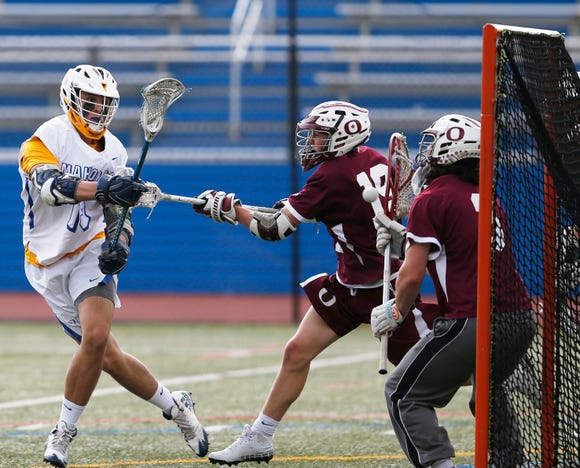 Mahopac's Anthony Corrado takes a shot on Ossining's goalie TJ Komosa as defender Michael Shevchik attempts to block the shot during Wednesdays' game at Mahopac High School on May 15, 2018.