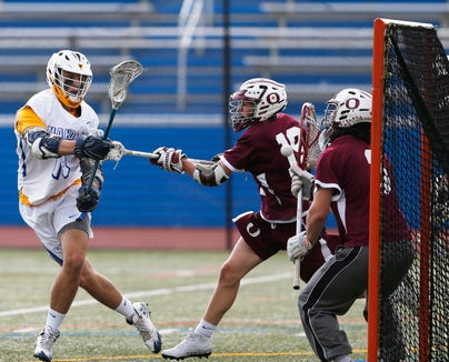 Mahopac's Anthony Corrado takes a shot on Ossining's goalie TJ Komosa as defender Michael Shevchik attempts to block the shot during Wednesdays' game at Mahopac High School on May 15, 2019.