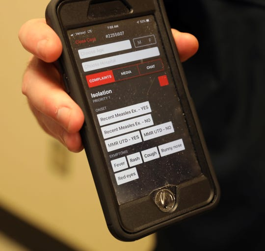 "Glenn Albin, R.N. and a paramedic with the South Orangetown ambulance corps, shows the ""isolation"" tab on a phone medical app called Twiage, at Montefiore Nyack Hospital, May 15, 2019."