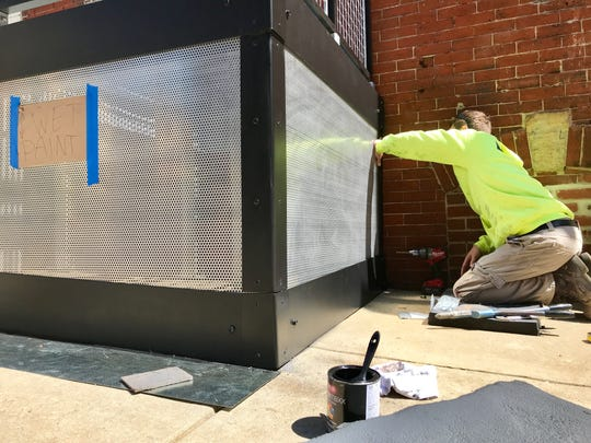 A worker paints the new patio bar coming to The Queen in Wilmington on Wednesday afternoon.