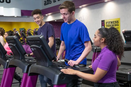 Planet Fitness staffer Chanice Ball helps teens workout on equipment during a Teen Summer Challenge. The gym is offering free workouts to teens ages 15-18 during the summer.