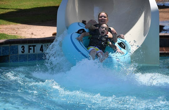 Melissa Boland and her son, Major Boland, 7, fly out of the Black Squall slide, one of 10 rides at Castaway Cove in this 2018 file photo. The waterpark opensfor the 2019 season this Saturday.