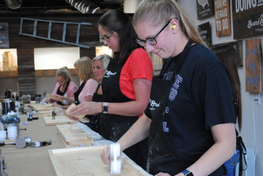 A group of ladies at Board & Brush wear ear plugs as they loudly distress their creations with hammers, screws, meat cleavers and other tools to create a weathered look to the wood.