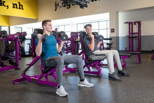 Brandon Campbell, left, and Keion Mitchell work out with dumbbells at a Planet Fitness.