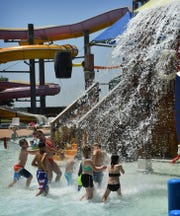 Children and adults hurry over to stand under the huge bucket dumping water on everyone in Buccaneer Bay at Castaway Cove Waterpark in this 2018 file photo. The park opens for the 2019 season Saturday at 10:30 a.m.
