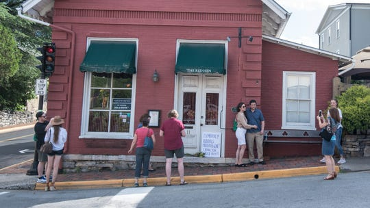 Passersby gather to take photos in front of The Red Hen restaurant last summer in Lexington, Va.