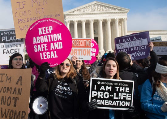 "Pro-choice activists hold signs Jan. 18 alongside anti-abortion activists participating in the ""March for Life"" in Washington, D.C."