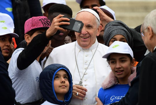 Pope Francis poses for a selfie photo with some refugees in St. Peter's Square.