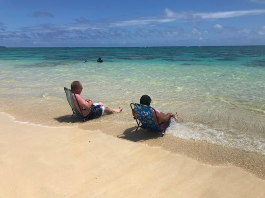 Visitors taking it easy on Lanikai Beach in Kailua, Hawaii.
