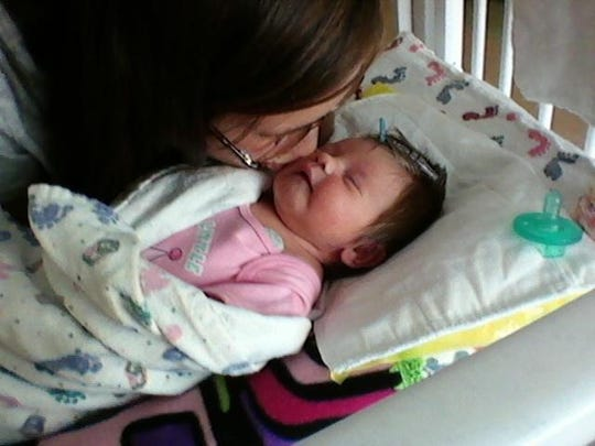 Emilee Strezinski kisses her daughter Amelia.
