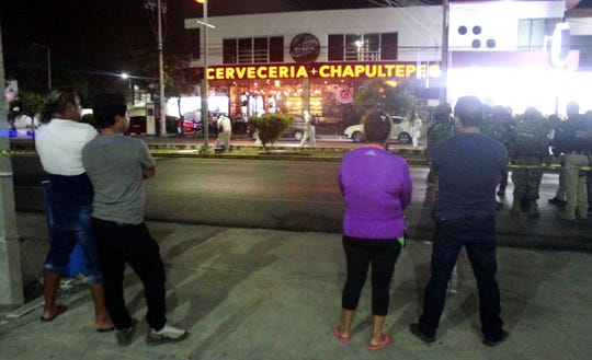 People observe the work of forensic experts at dawn in the area where an armed attack took place in a bar in the Mexican town of Playa del Carmen, Mexico, 14 May 2019. The attack, which occurred around 9:45 pm local time on Monday, left a preliminary death toll of one dead and 11 wounded, according to the Attorney General of Quintana Roo state.