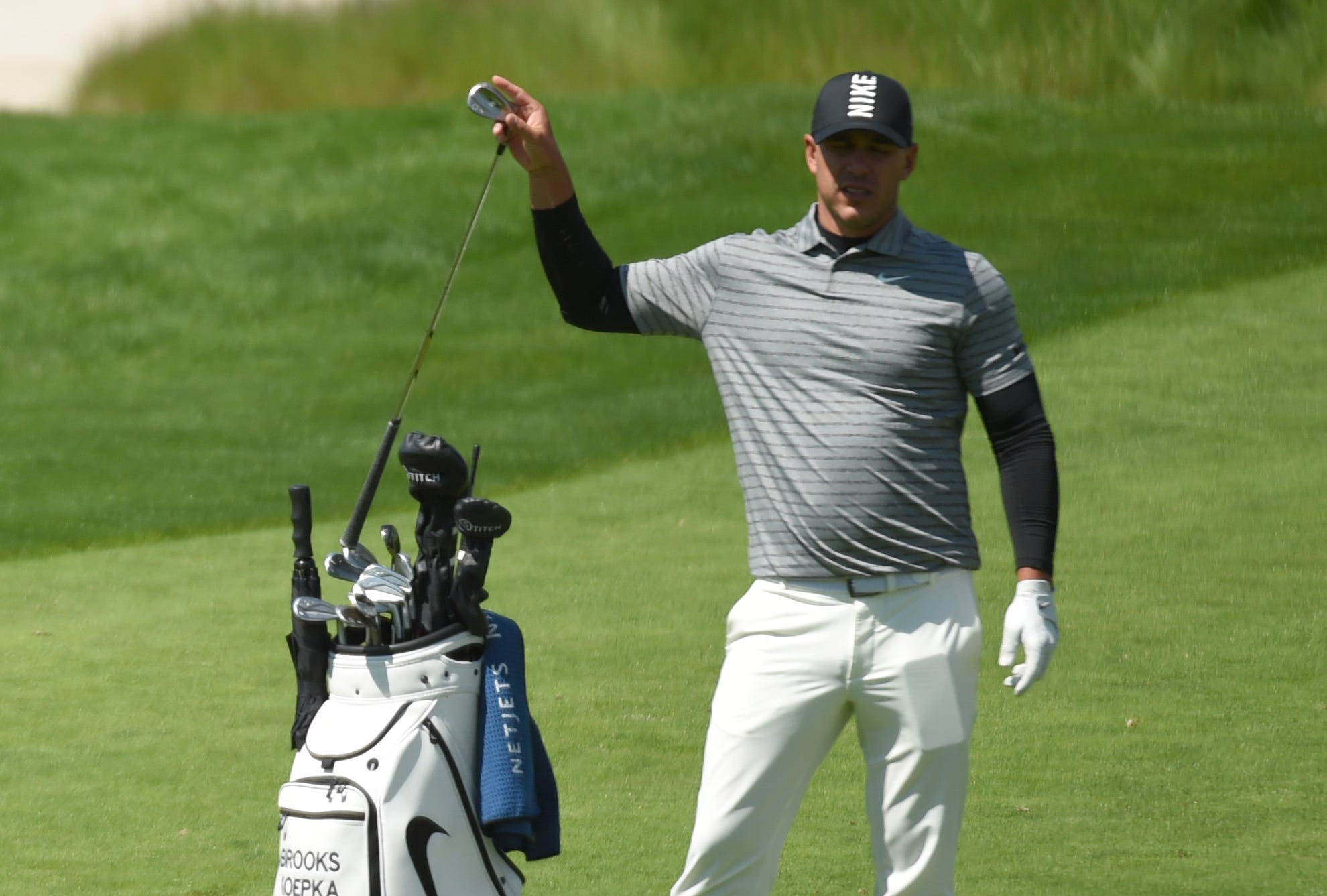 Practice round: Brooks Koepka, the defending champion, selects his club on the 18th hole.