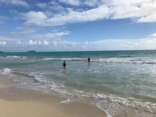 Swimmers head into the turquoise waters at Waimanalo Bay beach near Honolulu, Hawaii.