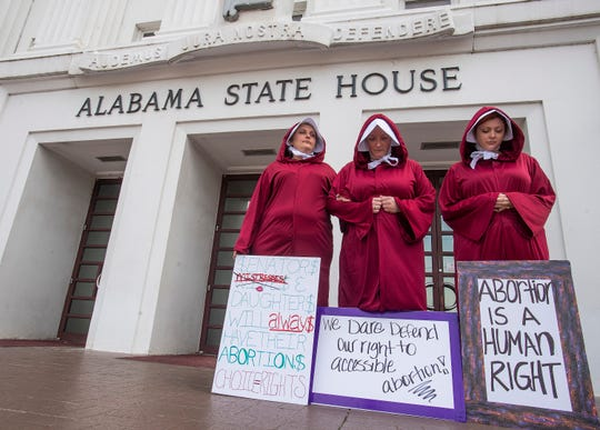 Bianca Cameron-Schwiesow, from left, Kari Crowe and Margeaux Hartline, dressed as handmaids, take part in a protest against HB314, the abortion ban bill, at the Alabama State House in Montgomery, Ala., on April 17, 2019.