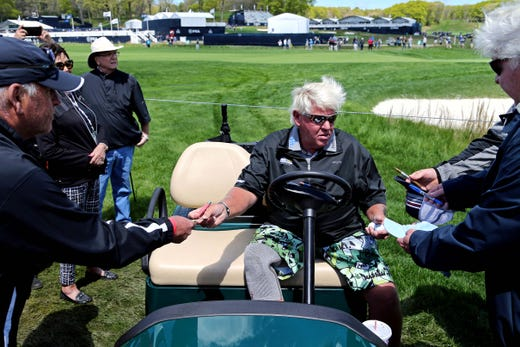 Practice round: John Daly signs autographs on the first hole.
