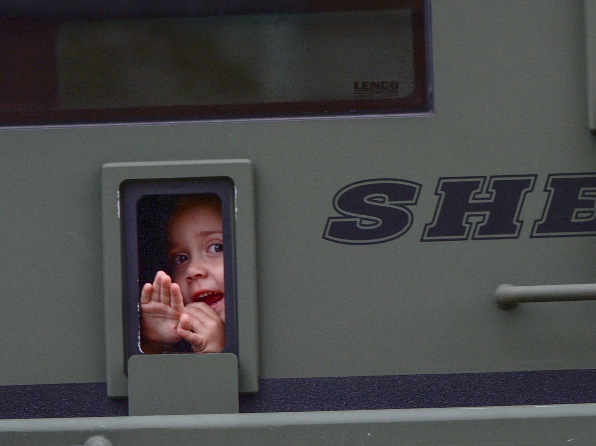 A girl waves from inside the Anderson County Sheriff SWAT truck during a procession of law enforcement riding to the 2019 Peace Officer Memorial Service Wednesday May 15, 2019. People attended to help honor the lives of officers lost in the line of duty.