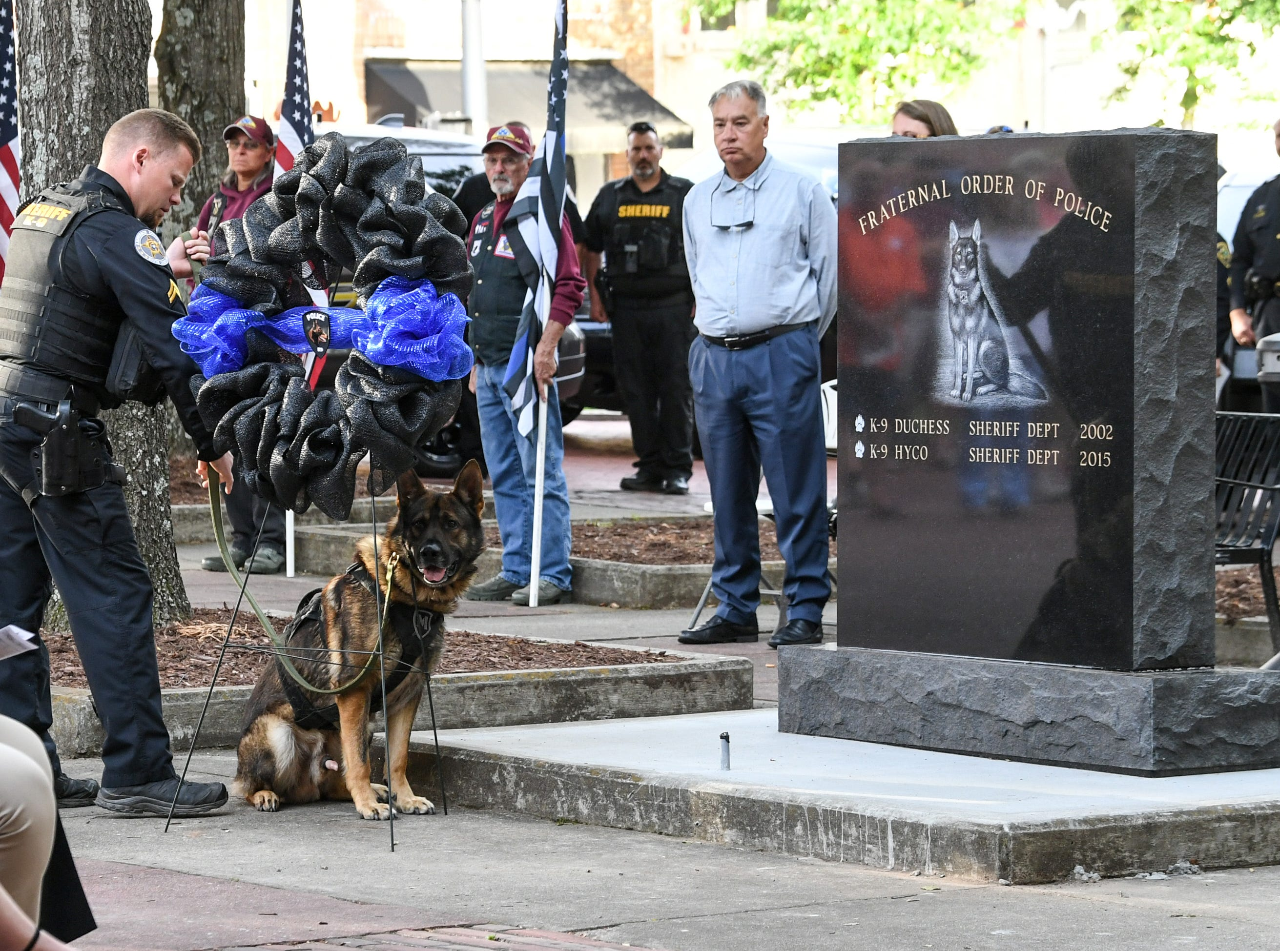 Eric Scott of the Anderson County Sheriff Office brings a K-9 wreath in front of the new monument for K-9, during the 2019 Peace Officer Memorial Service Wednesday May 15, 2019. People attended to help honor the lives of officers lost in the line of duty.