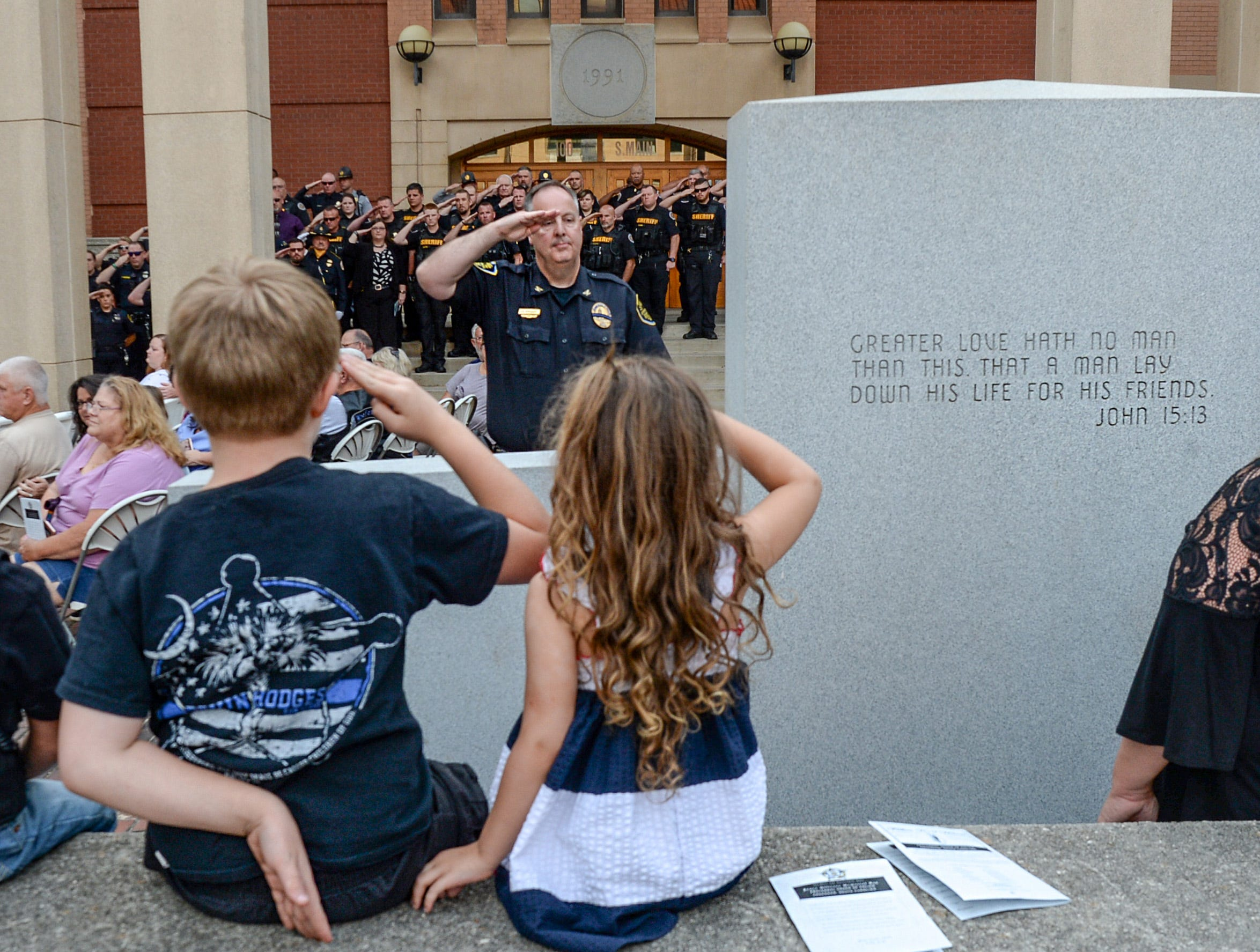 James Hodges, left, 9, and his sister Diana Hodges, 4, salute with Chief of Police Jim Stewart at the police monument in front of the Anderson County courthouse during the 2019 Peace Officer Memorial Service Wednesday May 15, 2019. People attended to help honor the lives of officers lost in the line of duty. Deputy Devin Pressley Hodges of the Anderson County Sheriff's office, the father of the two children, died in the line of duty in June 2017.
