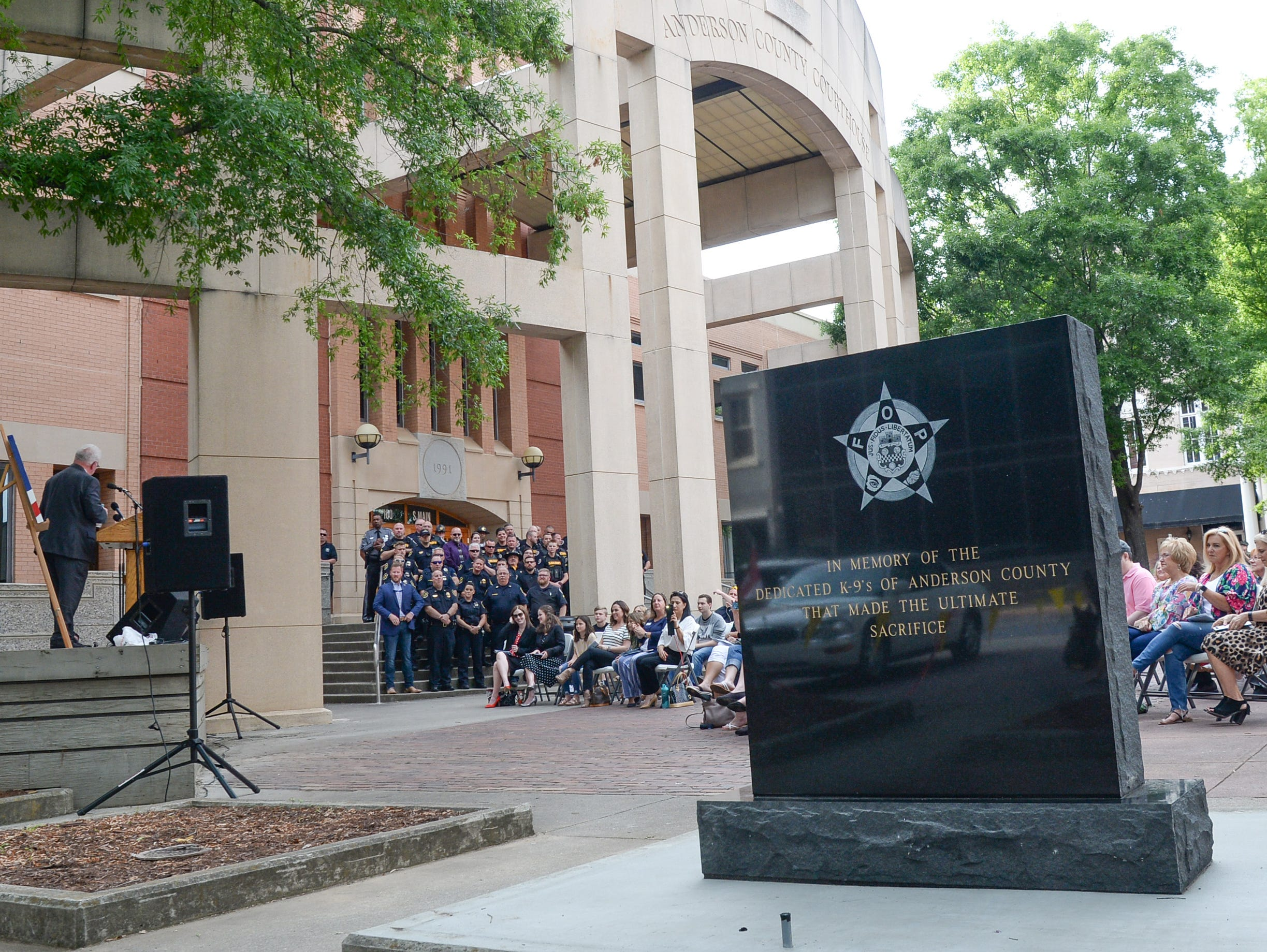 Keynote speaker Jackie Swindler, left, Director of the State Criminal Justice Academy, speaks near the new Fraternal Order of Police monument for fallen K-9 Duchess and Hyco, unveiled during the 2019 Peace Officer Memorial Service Wednesday May 15, 2019. People attended to help honor the lives of officers lost in the line of duty.