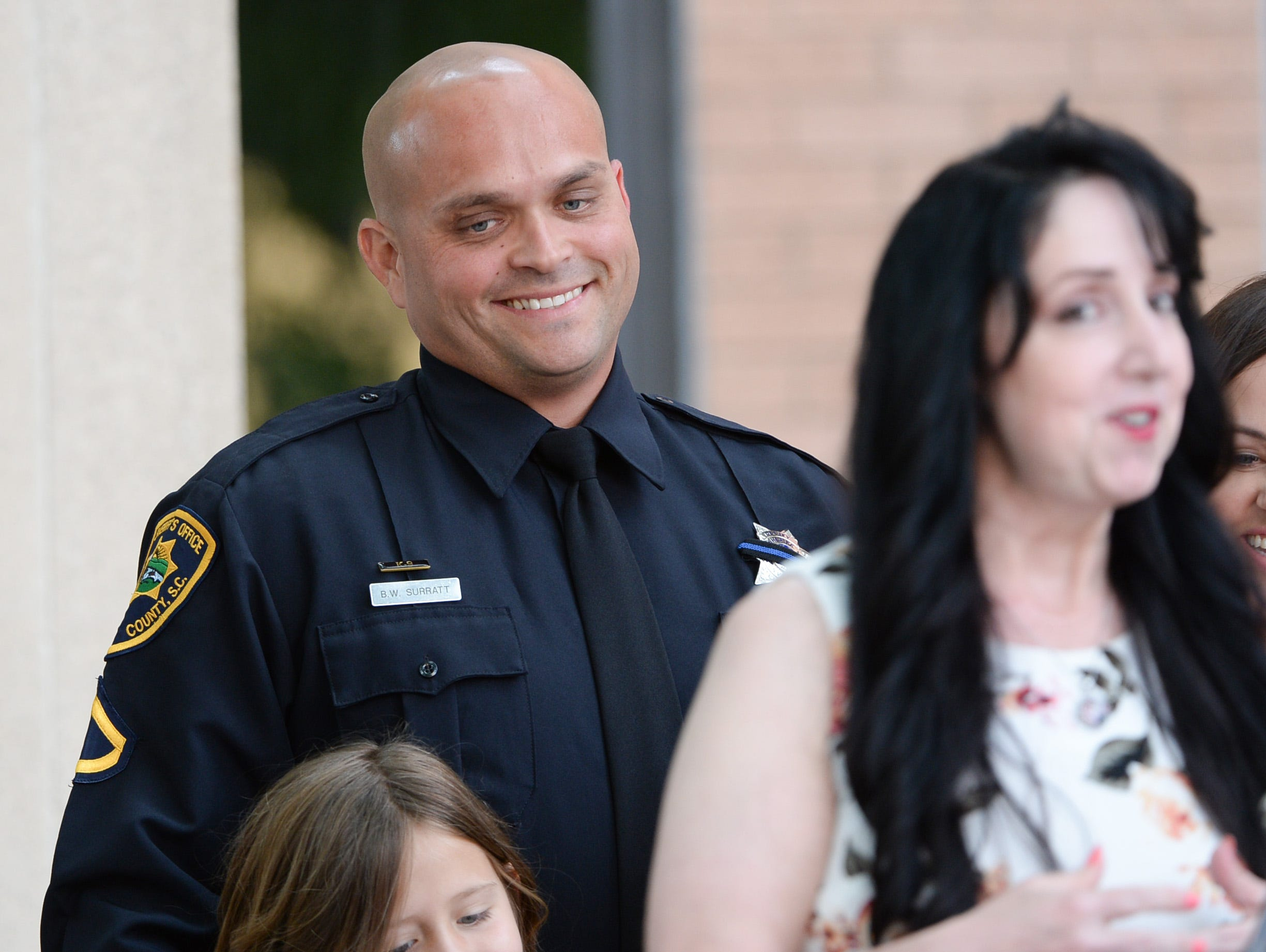 Brandon Surratt, left, of the Greenville Sheriff's Office, stands near artist Loreena Pantaleone, of Pennsylvania, who presented him a painting of Hyco, during the 2019 Peace Officer Memorial Service Wednesday May 15, 2019, in front of the Anderson County courthouse. People attended to help honor the lives of officers lost in the line of duty. Surratt, a former Anderson County Sheriff Deputy who lost his K-9 Hyco in the line of duty in 2015, spoke about serving as an officer.