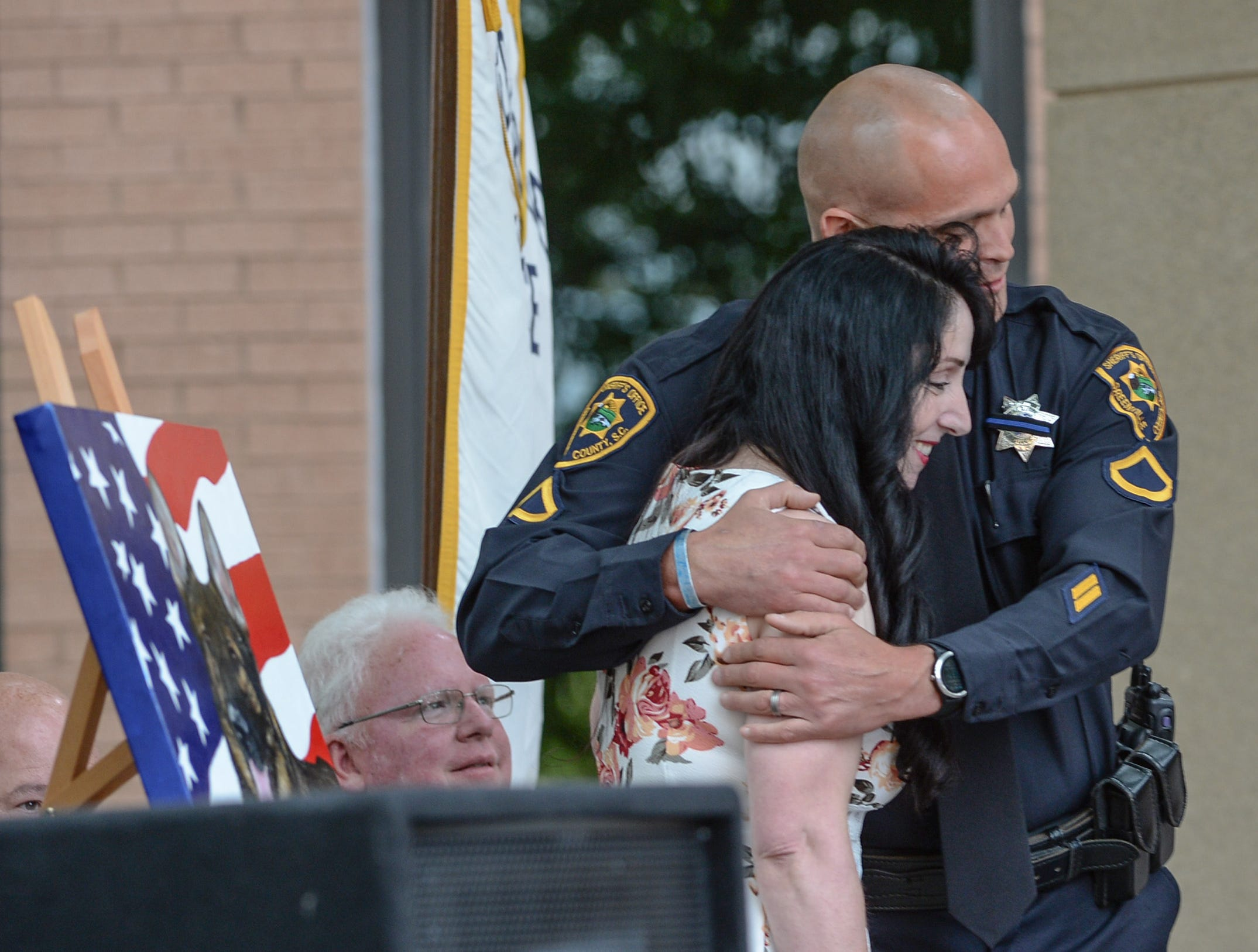 Brandon Surratt, right, of the Greenville Sheriff's Office, hugs artist Loreena Pantaleone, of Pennsylvania, who presented him a painting of Hyco, during the 2019 Peace Officer Memorial Service Wednesday May 15, 2019, in front of the Anderson County courthouse. People attended to help honor the lives of officers lost in the line of duty. Surratt, a former Anderson County Sheriff Deputy who lost his K-9 Hyco in the line of duty in 2015, spoke about serving as an officer.