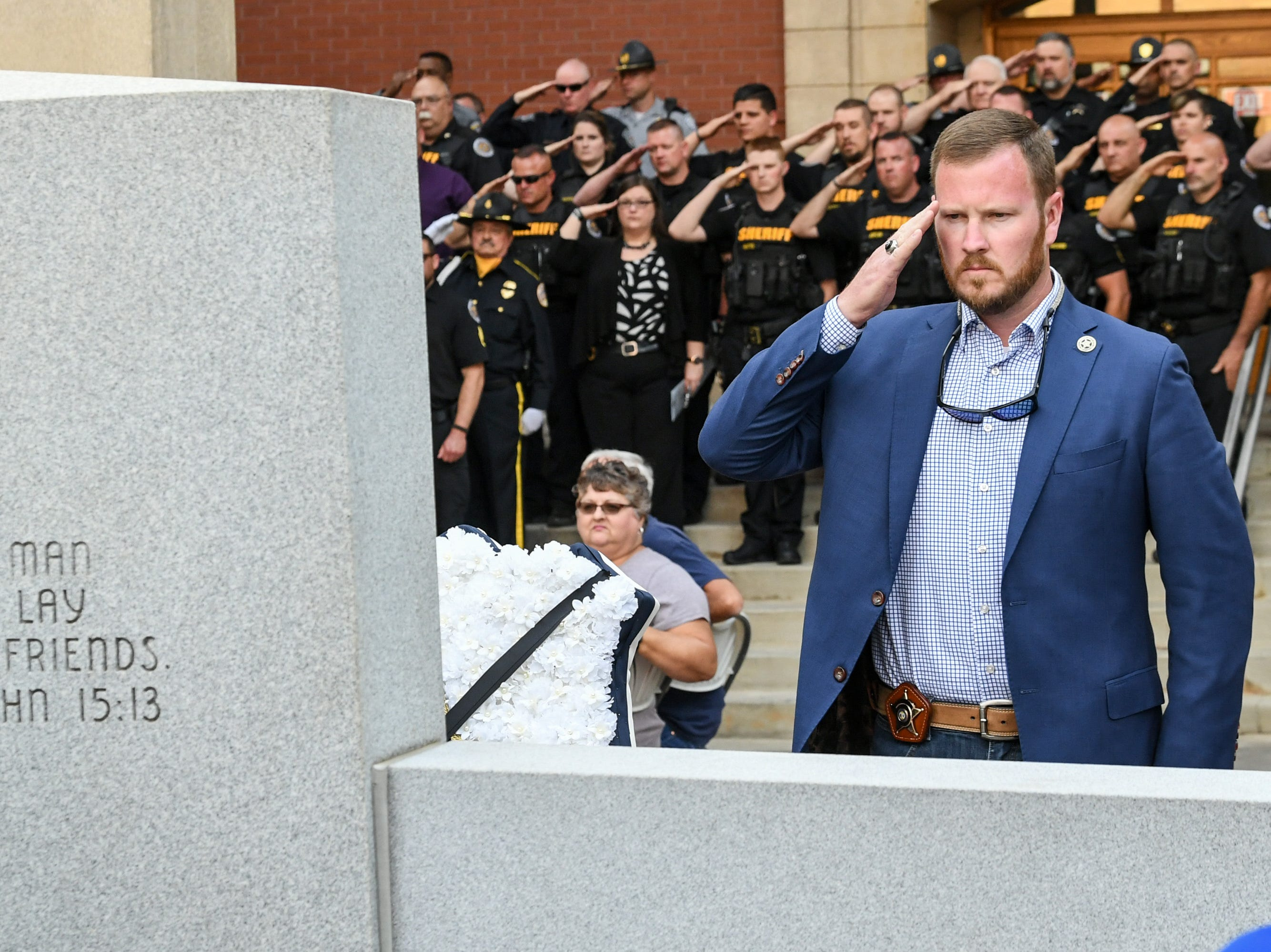 Sheriff Chad McBride and officers salute after laying a wreath with city Chief of Police Jim Stewart at the courthouse memorial, during the 2019 Peace Officer Memorial Service Wednesday May 15, 2019. People attended to help honor the lives of officers lost in the line of duty.
