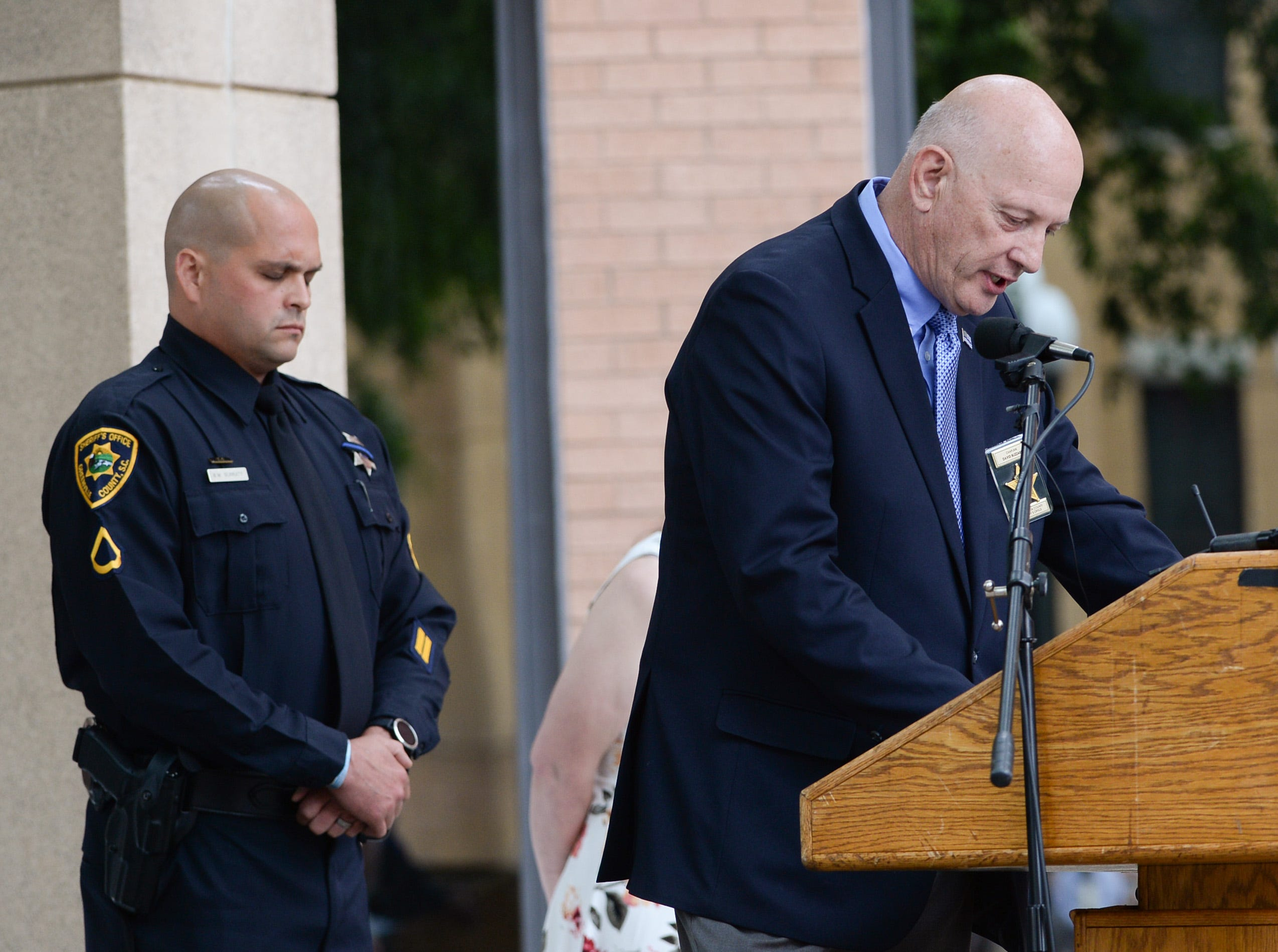 Brandon Surratt, left, of the Greenville Sheriff's Office, stands near Rev. David Blizzard offering the invocation during the 2019 Peace Officer Memorial Service Wednesday May 15, 2019, in front of the Anderson County courthouse. People attended to help honor the lives of officers lost in the line of duty. Surratt, a former Anderson County Sheriff Deputy who lost his K-9 Hyco in the line of duty in 2015, spoke about serving as an officer.