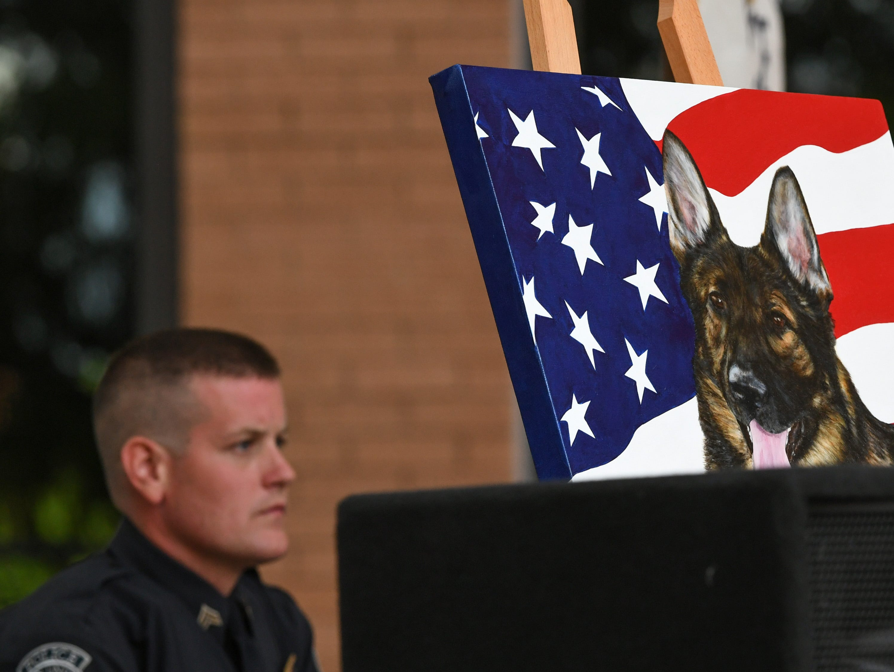 Chip Welborn, left, 2nd Vice President of Fraternal Order of Police Lodge #10 sits by a painting of K-9 Hyco during the 2019 Peace Officer Memorial Service in front of the Anderson County Courthouse Wednesday May 15, 2019. People attended to help honor the lives of officers lost in the line of duty. Loreena Pantaleone of Pennsylvania painted Hyco and gave it to Brandon Surratt of the Greenville County Sheriff's Office, who was Hyco's handler when he was shot in the line of duty in 2015 working with the Anderson County Sheriff's Office.