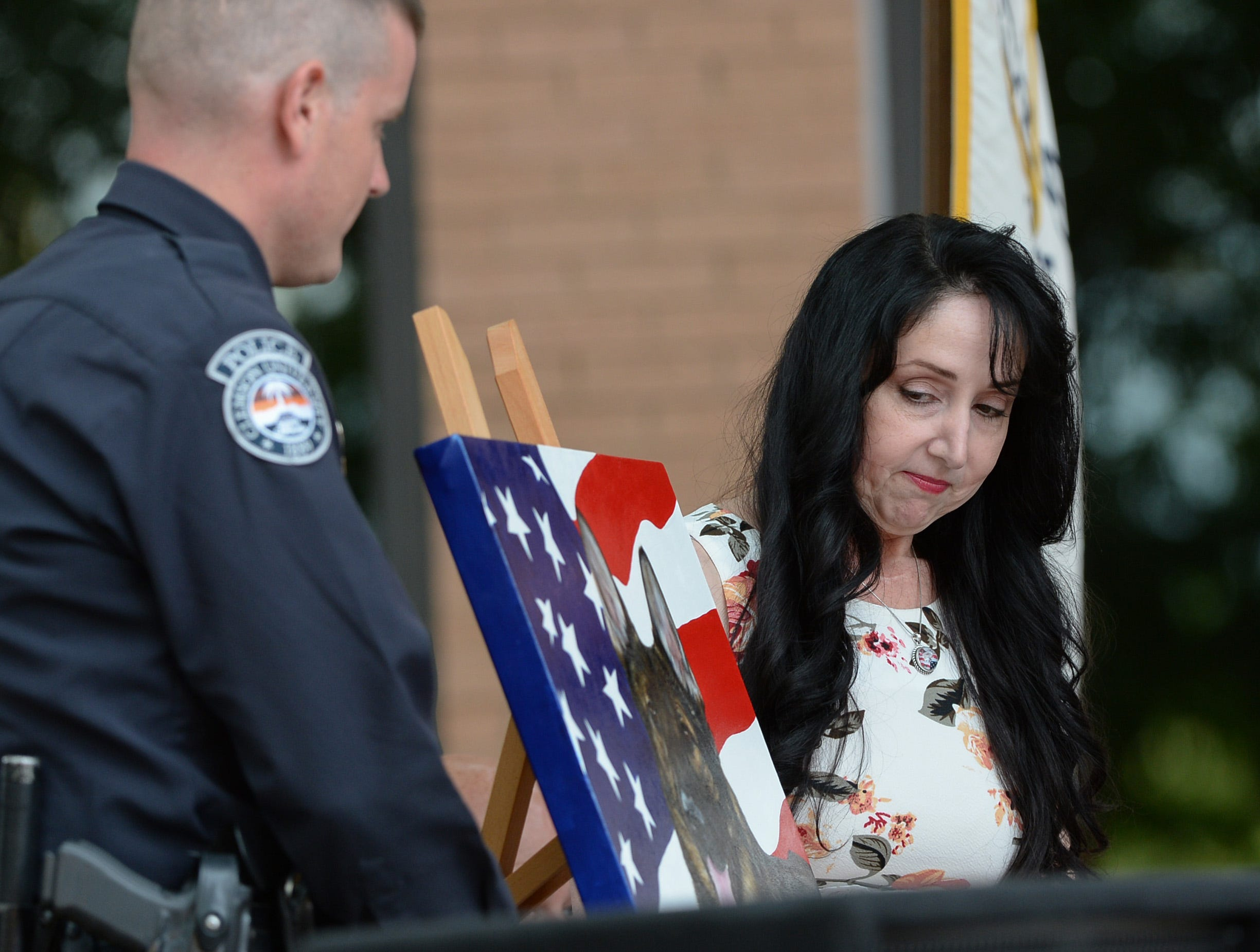 Chip Welborn, left, 2nd Vice President FOP Lodge 10, stands near artist Loreena Pantaleone, of Pennsylvania, who presented Brandon Surratt a painting of Hyco, during the 2019 Peace Officer Memorial Service Wednesday May 15, 2019, in front of the Anderson County courthouse. People attended to help honor the lives of officers lost in the line of duty. Surratt, a former Anderson County Sheriff Deputy who lost his K-9 Hyco in the line of duty in 2015, spoke about serving as an officer.