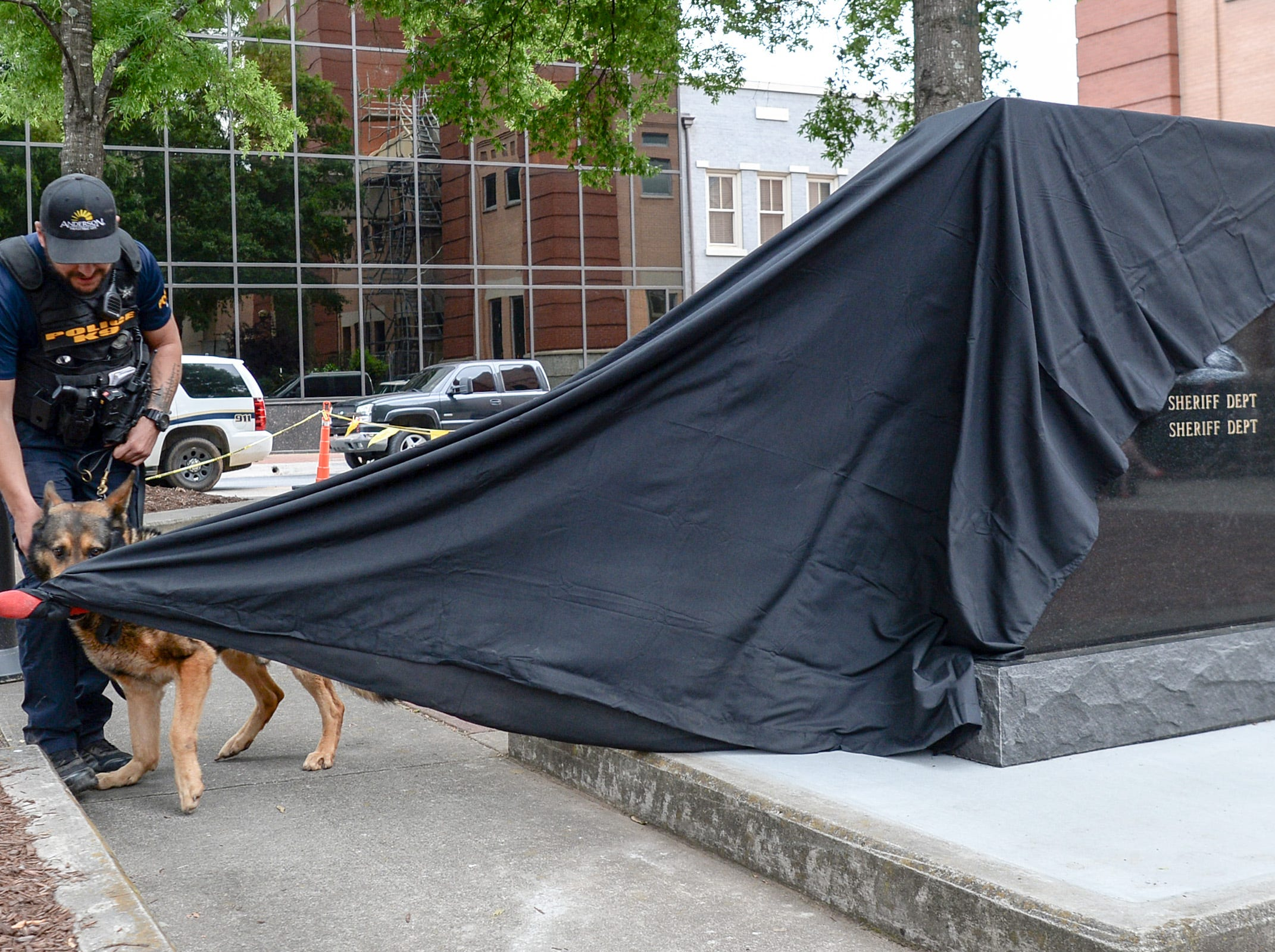 Cpl. Cory Barrow stands near his K-9 Peppa, pulling to unveil the new Fraternal Order of Police monument for fallen K-9 Duchess and Hyco, during the 2019 Peace Officer Memorial Service Wednesday May 15, 2019. People attended to help honor the lives of officers lost in the line of duty.