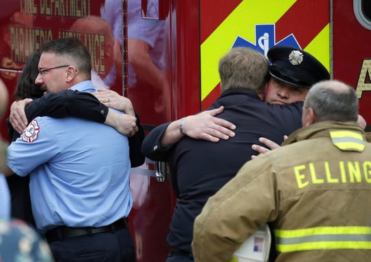 Those gathered at Brettschneider-Trettin-Nickel Funeral Chapel hug after the procession for a firefighter who was shot and killed while responding to a medical call at the Valley Transit Center Thursday, May 16, 2019, in Appleton, Wis.