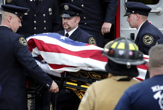 A firefighter who was shot and killed while responding to a medical call at the Valley Transit Center is draped in an American Flag and taken out of an ambulance at Brettschneider-Trettin-Nickel Funeral Chapel which ended a procession that went from Milwaukee to Appleton at Thursday, May 16, 2019, in Appleton, Wis.