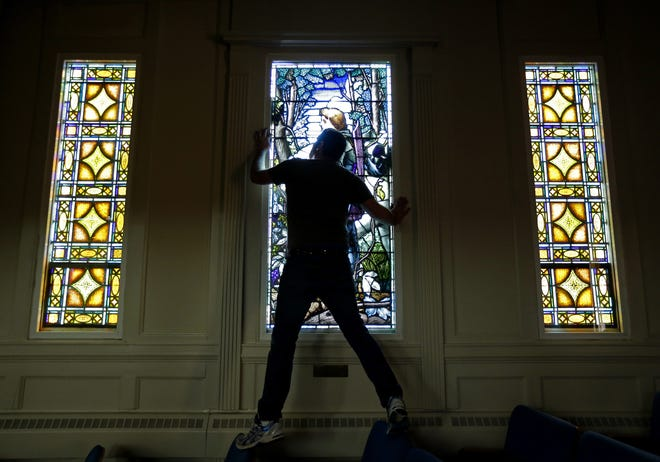 A Coventry Glassworks & Gallery employee installs a window in Lawrence University's Memorial Chapel in 2015.