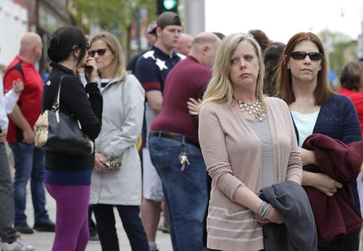 Citizens linger in silence following a procession for a firefighter shot and killed while responding to a medical call at the Valley Transit Center moves along College Avenue Thursday, May 16, 2019, in downtown Appleton, Wis.  Dan Powers/USA TODAY NETWORK-Wisconsin