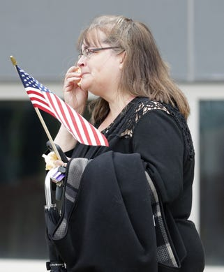 Beth Jasiak, assistant to the Appleton Police Department chief, wipes tears from her eyes during a procession for a firefighter shot and killed while responding to a medical call at the Valley Transit Center moves along College Avenue Thursday, May 16, 2019, in downtown Appleton, Wis.  Dan Powers/USA TODAY NETWORK-Wisconsin