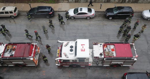 Milwaukee firefighters return to their trucks after being part of an honor guard for an Appleton firefighter Thursday, May 16, 2019 outside the Milwaukee County Medical Examiner's Office, 933 W. Highland Ave. in Milwaukee, Wis. The firefighter was shot, along with three other people, while at the scene of a medical emergency, according to an Appleton Fire Department news release early Thursday morning. The firefighter, a 14-year veteran whose name was not released, died at an Appletom area hospital.   MARK HOFFMAN/MILWAUKEE JOURNAL SENTINEL