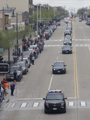 Police vehicles participate in a procession for a firefighter shot and killed while responding to a medical call at the Valley Transit Center moves along College Avenue Thursday, May 16, 2019, in downtown Appleton, Wis.  Dan Powers/USA TODAY NETWORK-Wisconsin
