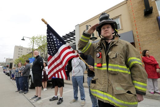 A Neenah-Menasha firefighter salutes during a procession for a firefighter shot and killed while responding to a medical call at the Valley Transit Center moves along College Avenue Thursday, May 16, 2019, in downtown Appleton, Wis.  Dan Powers/USA TODAY NETWORK-Wisconsin