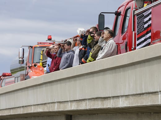 Members of the Eldorado and Rosendale Fire Departments pay respect to a fallen Appleton firefighter Thursday, May 16, 2019 on the Interstate 41 Lincoln Road overpass as his procession from the Milwaukee Medical Examiner's office to Brettschneider-Trettin-Nickel Funeral Chapel in Appleton passes by. The firefighter was killed when he was shot, along with three other people at a medical emergency call at the Valley Transit Center in downtown Appleton. Doug Raflik/USA TODAY NETWORK-Wisconsin