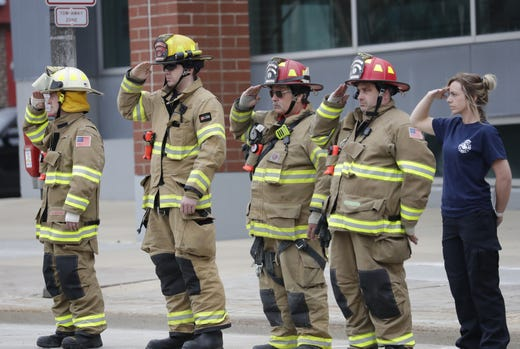 Members of the Suamico Fire Department salute during a procession for a firefighter shot and killed while responding to a medical call at the Valley Transit Center moves along College Avenue Thursday, May 16, 2019, in downtown Appleton, Wis.  Dan Powers/USA TODAY NETWORK-Wisconsin