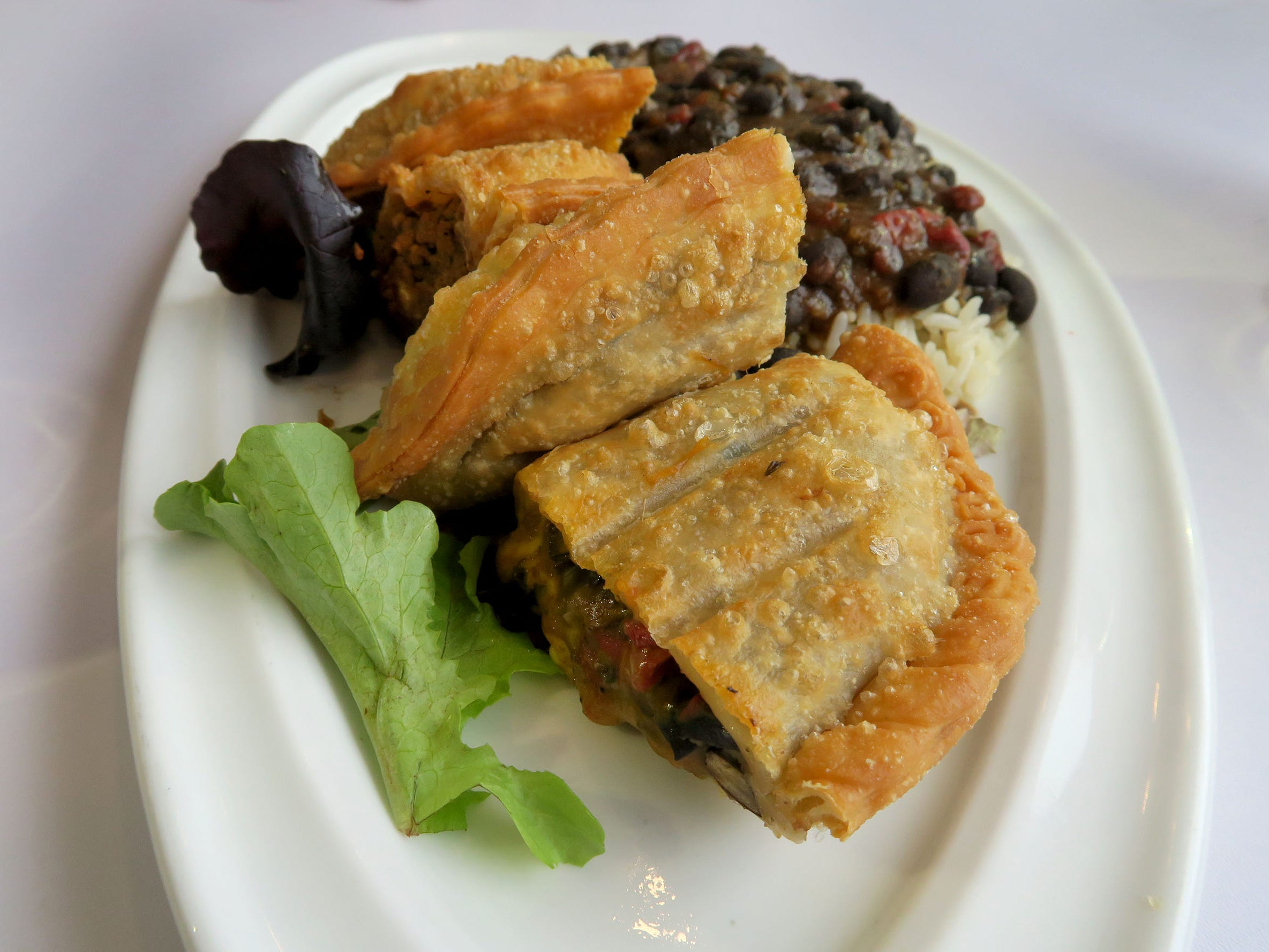 """The Empanada Combo served with a side of black beans and white rice at """"Caneda's White Rooster,"""" a year-old Toms River-based Cuban restaurant on Fischer Boulevard."""